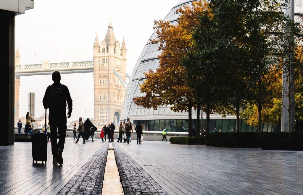 Una persona con una valigia in penombra cammina in direzione del Twoer Bridge a Londra, nascosto da una cupola in vetro.