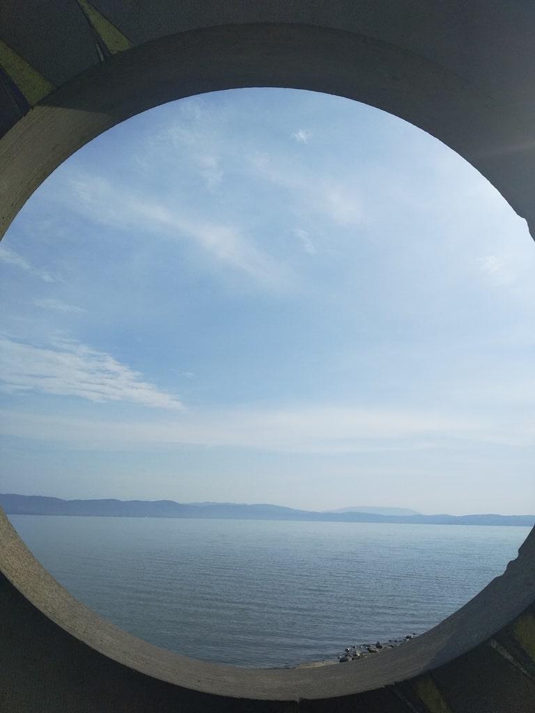 Vista del Lago di Trasimeno attraverso un cerchio di cemento.