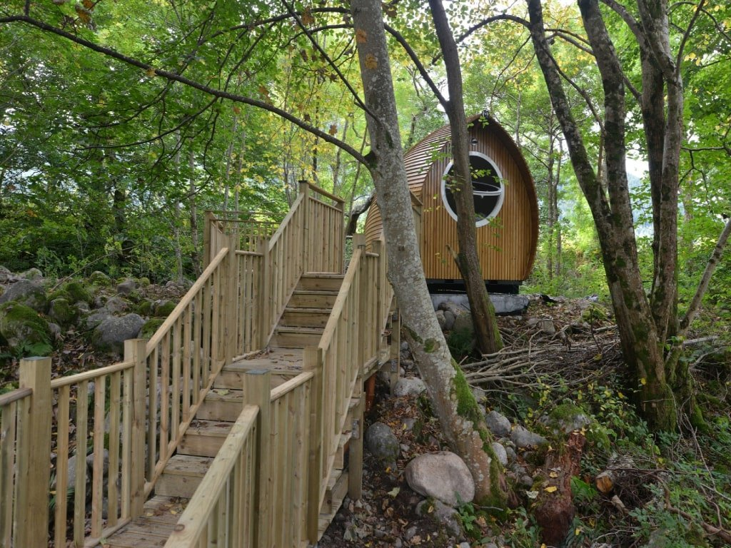 Una capanna in legno a forma di uovo, inserita in un bosco con delle scale a raggiungerla.