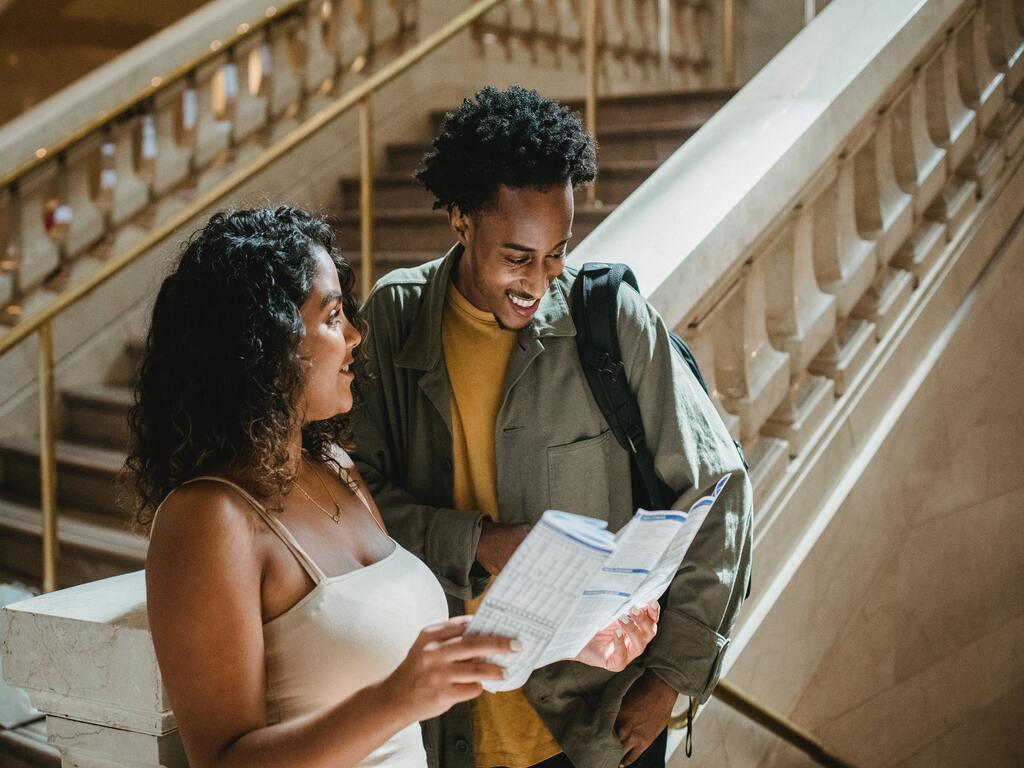 Un ragazzo e una ragazza leggono una mappa sulla scalinata di un museo durante un free walking tour.