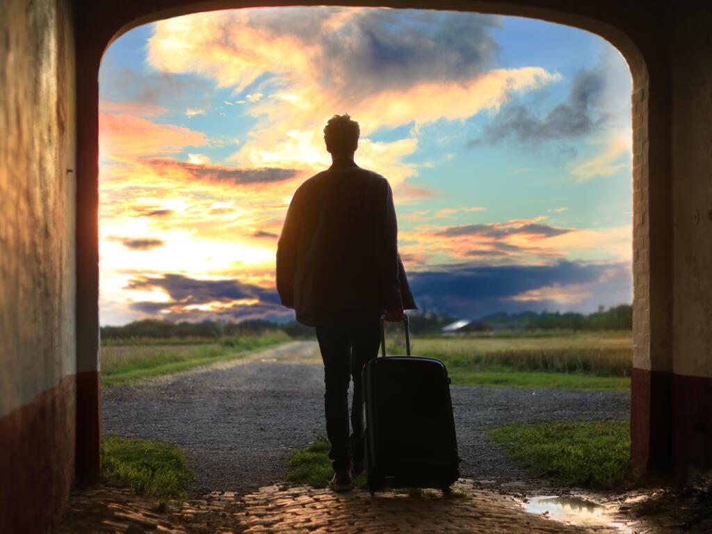 Un ragazzo con una valigia si incammina fuori da una galleria verso il tramonto