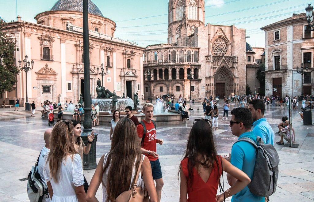 Un gruppo di ragazzi prendono parte a un free walking tour in una piazza italiana.