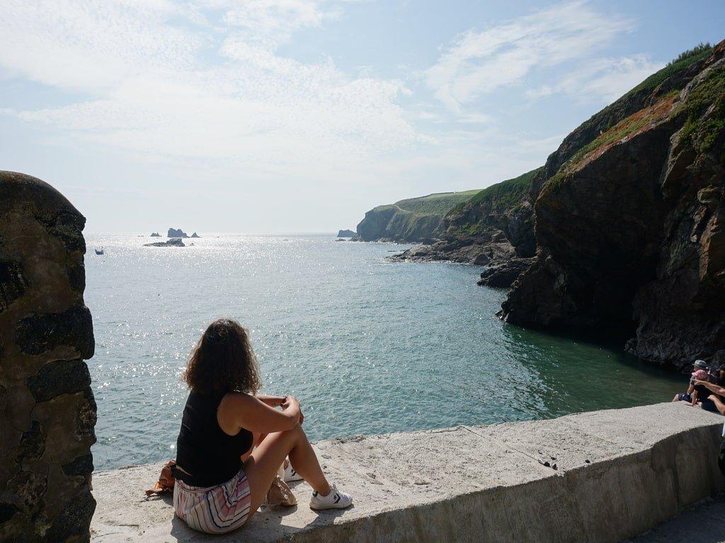 Una ragazza è seduta su di un muretto e guarda l'oceano e gli scogli della costa.