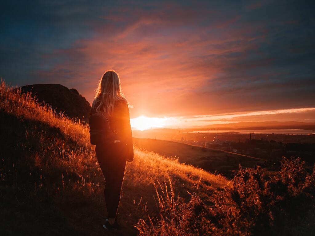 Una ragazza guarda il tramonto dalle colline verso una città