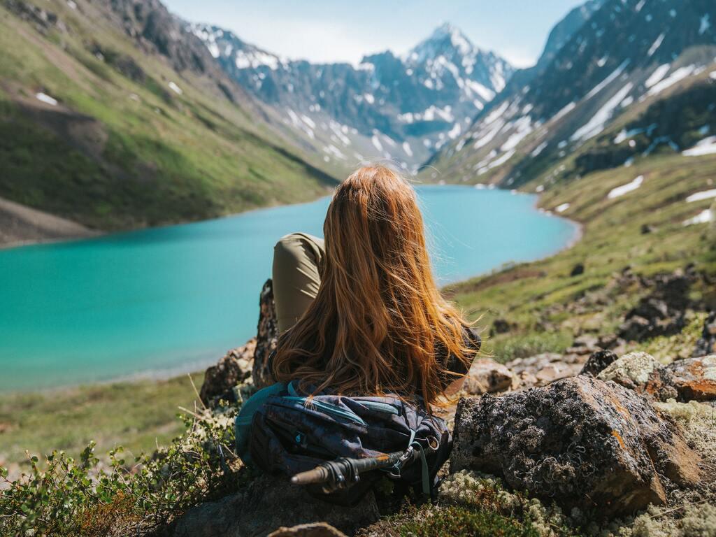 Una ragazza con i capelli castani, di spalle, è stesa ad osservare un lago e le montagne innevate