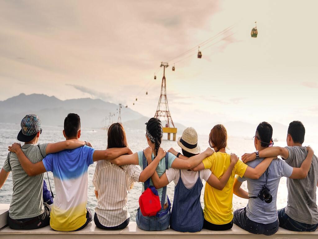 Un gruppo di ragazzi, uno accanto all'altro, si abbracciano osservando il mare e una funivia