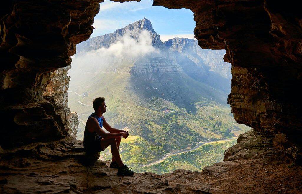 Un ragazzo, dall'apertura di una grotta, contempla la valle sottostante