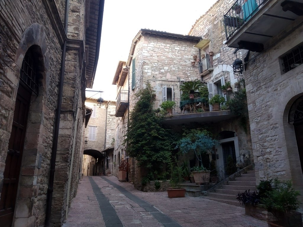 Una visuale su alcuni degli edifici storici che si affacciano in una vietta di Assisi. In particolare, una casa decorata da molte piante e fiori.