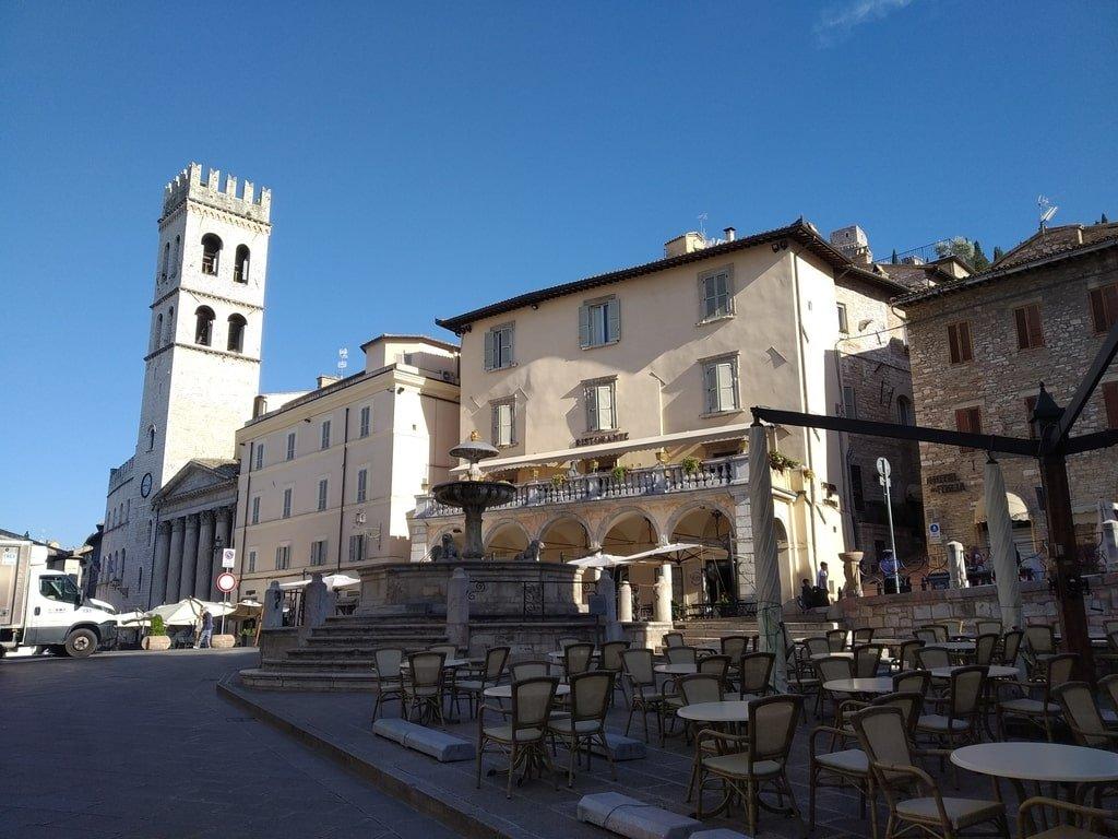 Piazza del comune ad Assisi, con la Fontana dei tre leoni e i tavolini di un bar esterno.