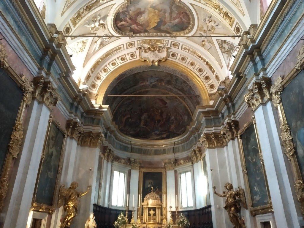 L'interno della Cattedrale di San Rufino ad Assisi, con le pareti riccamente decorate da mosaici e dettagli dorati.