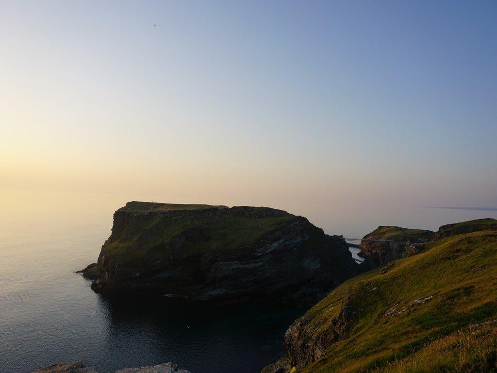 Vista della penisola che ospita il castello di Tintagel, in Cornovaglia, durante l'ora del tramonto.