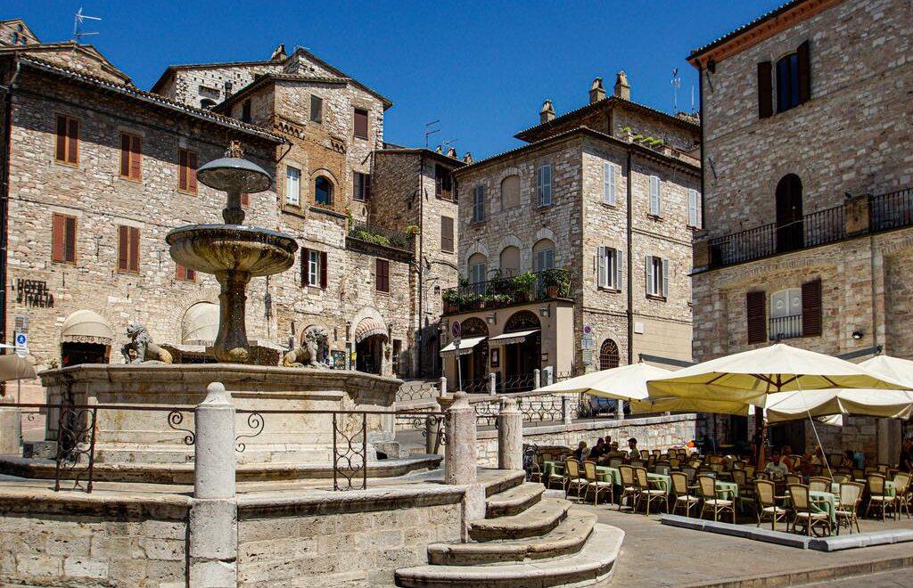 La piazza del comune di Assisi con la fontana dei tre leoni e, sullo sfondo, i palazzi storici in mattoni del borgo umbro.
