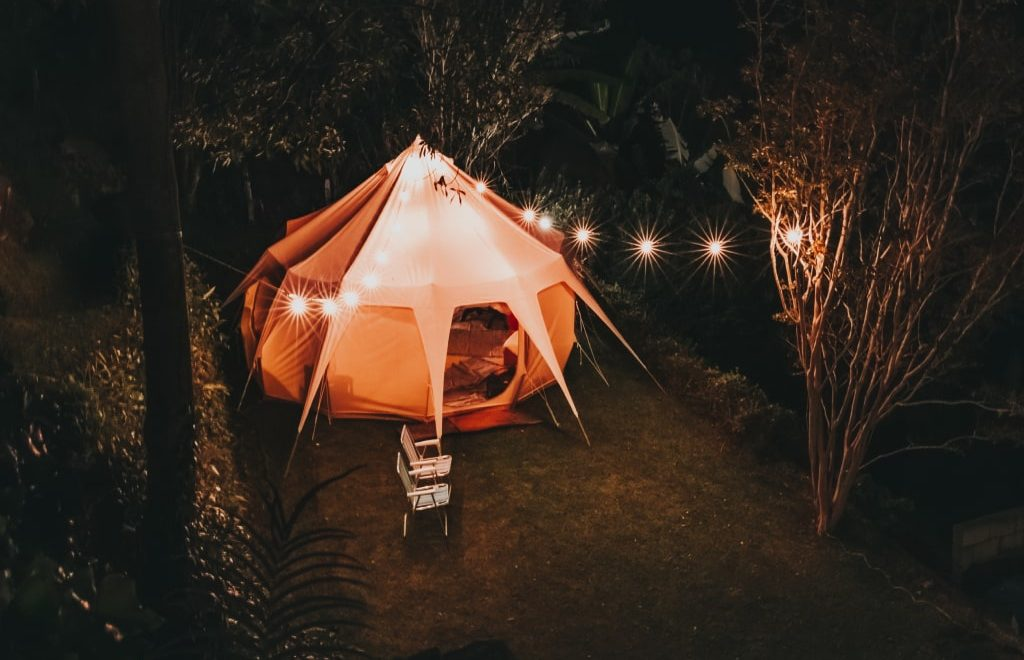 Una tenda bianca piazzata ai bordi di un bosco, illuminata da luci appese durante la notte.
