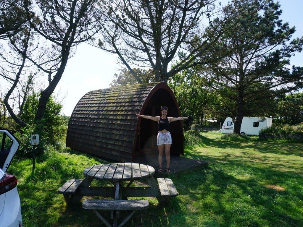 Una ragazza di fronte a una capanna in legno in un campeggio in Cornovaglia