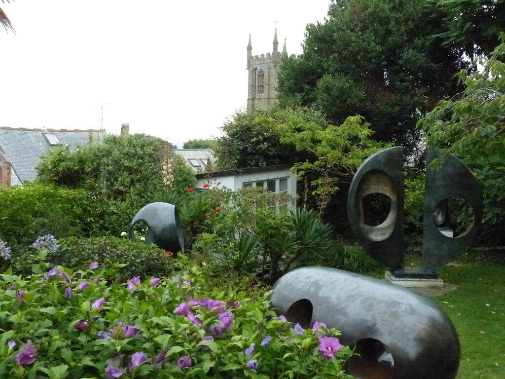 Alcune sculture in pietra scura immerse tra i fiori della Barbara-Hepworth Museum and Sculpture Garden
