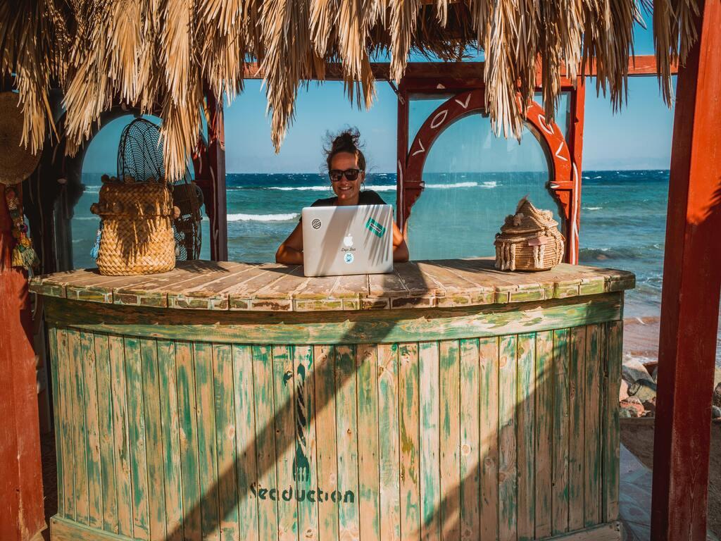 Una ragazza lavora con il suo computer al bancone di un bar sulla spiaggia.