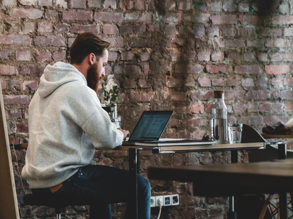 Un ragazzo lavora con il suo computer a un tavolo di un coffee shop dalle pareti in mattoni.