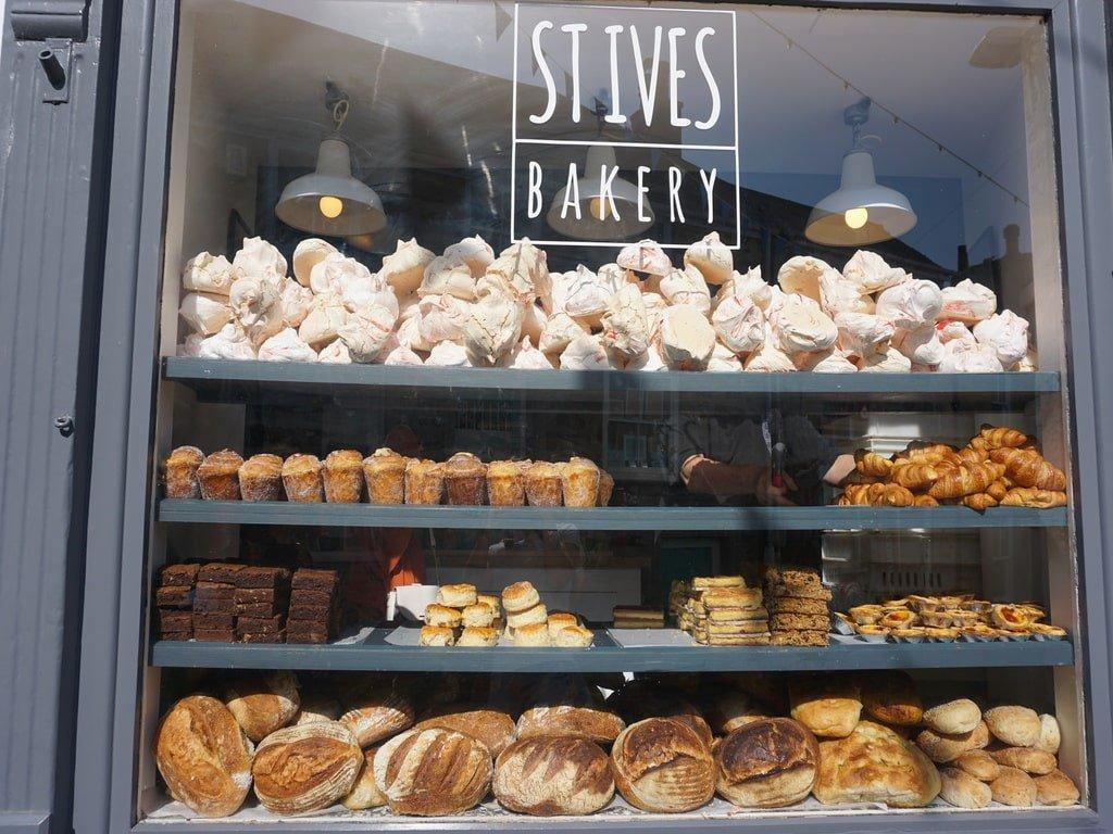 La vetrina di una pasticceria di St Ives con pane, dolci e meringhe posizionati sugli scaffali.