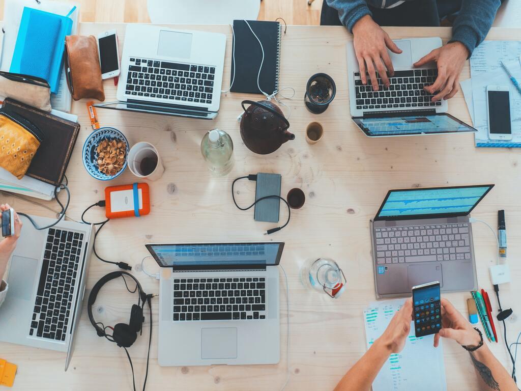 Cinque persone lavorano con cellulari e computer a un tavolo, con una visuale che mostra le loro mani e le tastiere dall'alto.