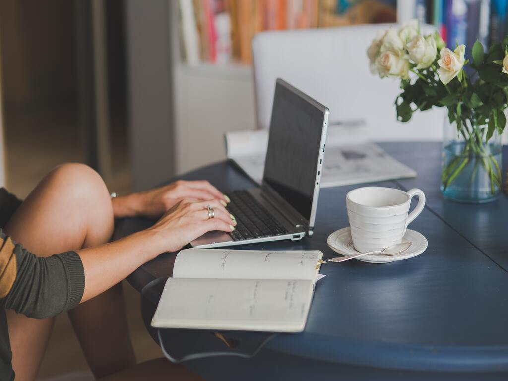 Le mani di una persona che lavora al suo computer mentre annota delle informazioni su di un libriccino accanto a una tazza di caffè.