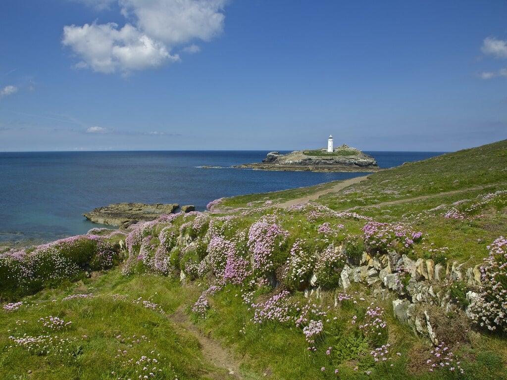 Vista di una piccola isola con un faro bianco dal punto panoramico di Godvrery Viewpoint a St Ives, Cornovaglia.