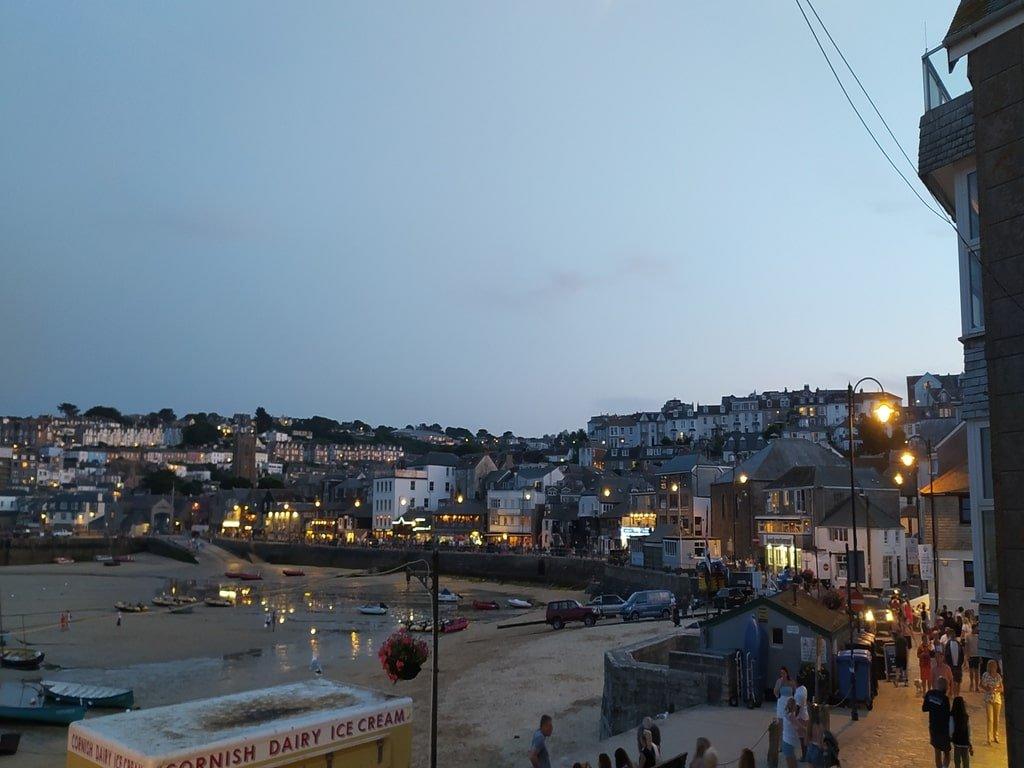 Vista del porto e del lungomare di St Ives, con ristorantini affollati dai turisti, durante la sera.