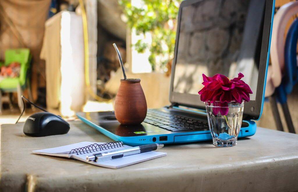 Un computer portatile blu su di un tavolo con un mouse, un'agenda, una tazza di caffè e un bicchiere con dentro un fiore rosa.