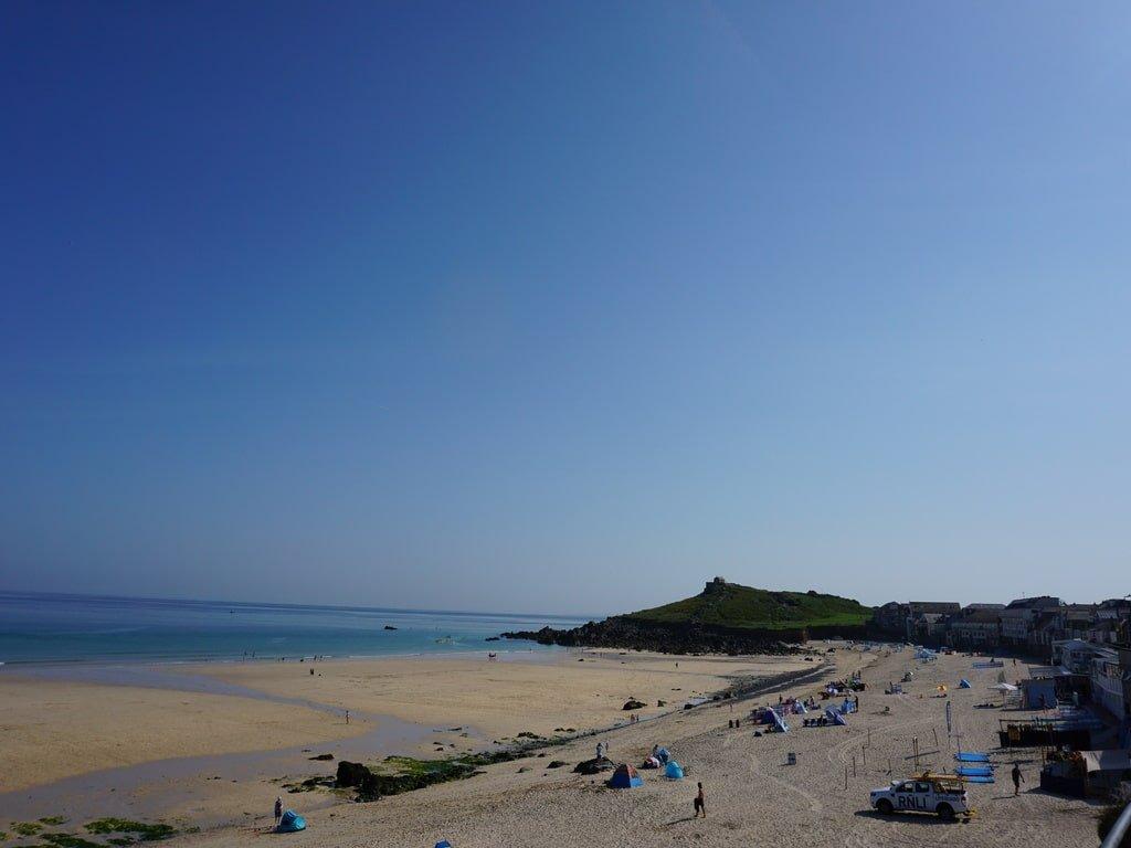 Vista della spiaggia di Porthmeor e della collina di The Island a St Ives durante il giorno.