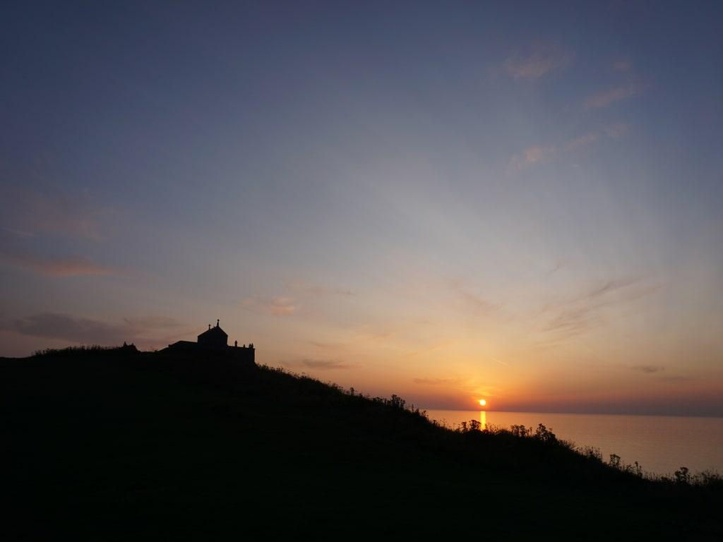 Vista del tramonto sull'oceano con la silhouette scura della chiesa di San Nicola a St Ives, in Cornovaglia.