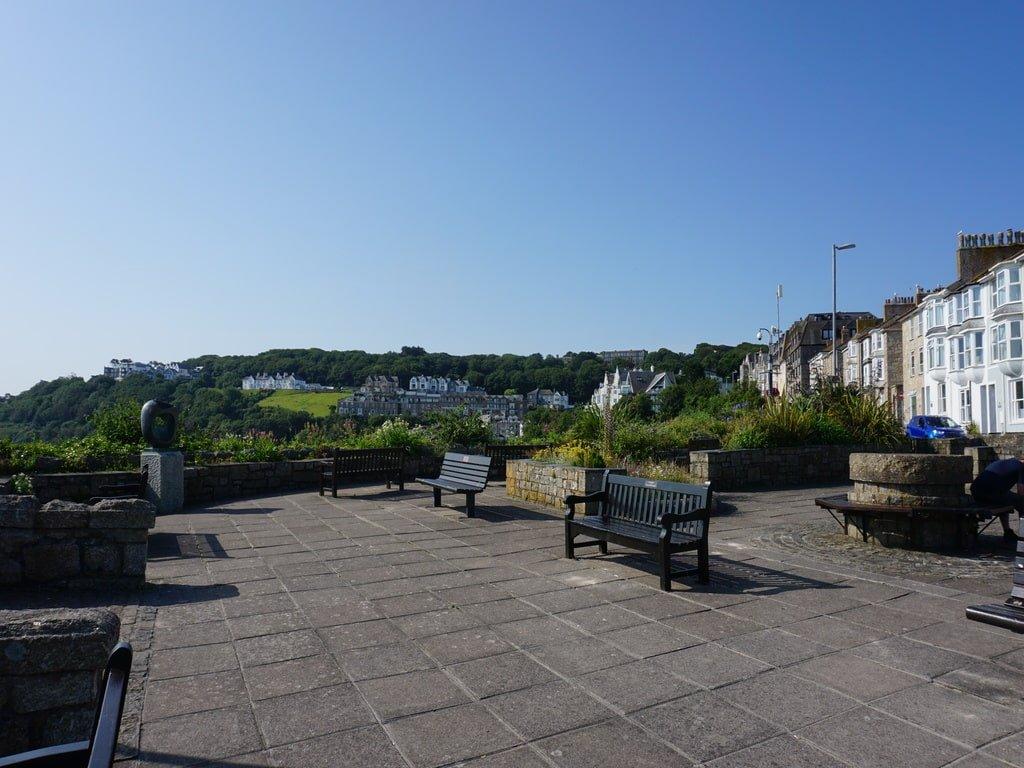 Panchine e poche case che si vedono voltando le spalle al punto panoramico The Terrace a St Ives.
