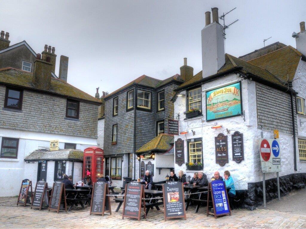L'esterno, con tavoli in legno nero, molti cartelli pubblicitari a descrivere i prodotti, del pub The Sloop Inn a St Ives, in Cornovaglia.