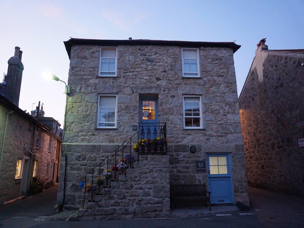 Un piccolo cottage in pietra, decorato da fiori, a St Ives in Cornovaglia.